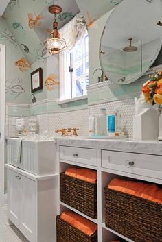 Playful blue and orange kids' bedroom features wicker baskets place on shelves below a marble top white vanity fitted with glass knobs and a carrera m. Nina Campbell, Blue Subway Tile, Bath Tiles, White Vanity, Hexagon Tiles, Glass Knobs, Laundry Room Design, Marble Countertops, Interior Design Studio