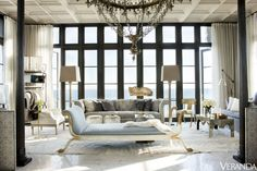 Gridded windows overlooking the Gulf of Mexico offer a masculine contrast to the living room's romantic allure.