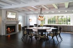 "To create a party-friendly focal point for a large dining room, Susana Simonpietri of Chango & Co. specified a large round dining table, complete with a lazy Susan. ""Both the chandelier and round dining table were custom made for this space,"" she says. ""The simplicity of the original architecture creates a natural ebb and flow while gauzy curtains soften the natural light."""