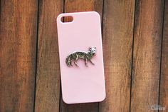A hand-hammered silver plated fox pendant laid on our pink hard shell case. Handmade to order!