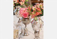 Jarras e bules de prata podem receber flores. Sob cada peça, vasos de cabeça para baixo dão altura ao arranjo. Produção Luana Prade