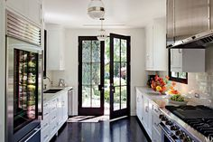 Natural light streams in through towering French doors in this Los Angeles kitchen designed by Madeline Stuart and equipped with pendant lights from BK Antiques, a Sub-Zero refrigerator, a Blanco sink with Kallista fittings, and a Viking range.