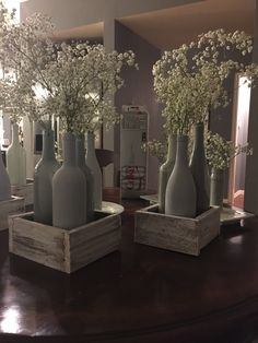 DIY center piece design for any party! Different shades of gray painted wine bottles with white washed wood boxes finished off with baby breath
