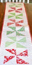 his simple Christmas Pinwheel Table Runner is one of the easiest no-nonsense Christmas quilt table runner patterns. Using convenient charm squares in red, green, and white, this pieced table runner could easily be made in colors for other seasons, too!