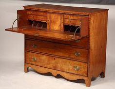 "TIGER MAPLE BUTLER'S CHEST - Late 18th to early 19th c. New England Solid Maple Butler's Chest with overhanging single plank top, drop-front faux upper drawer concealing desk with cabinet, letter drawers and valanced compartments, three graduated drawers below, all with beaded edge, cast brass oval drop bails, boldly shaped skirt and bracketed, slightly swept legs. 40 1/4"" x 45"" x 19 3/4'."