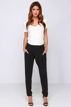 Take on a chic new look with the menswear-inspired Trousers and His Black Pants! Textured poly offers a classic look through these high-waisted pants, with box pleats, rounded front pockets, and a unique asymmetrical double button front. Relaxed legs taper to an ankle cut, finished with exposed gunmetal zipper cuffs. Back flap pockets have hidden buttons. Zip fly/button and hook closure. Partially lined in black satin. 100% Polyester. Hand Wash Cold. Imported.
