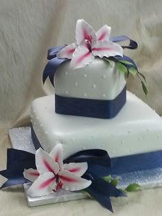 The Cakebox Bahamas: 2-tier square fondant finished cake with gumpaste lillies and leaves.