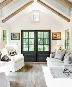 """Inside the Low Country, exposed beams and 7"""" oak hardwood flooring provide a warm contrast to the white shiplap walls."""