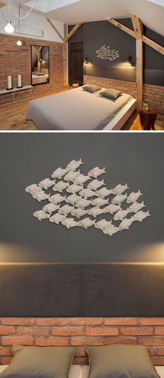 In this bedroom, a wall has been painted dark gray and features a delicate piece of artwork in the form of a school of fish.