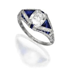PLATINUM, DIAMOND AND SAPPHIRE RING, CIRCA 1920.    Set in the center with a cushion-shaped diamond weighing approximately 2.60 carats, flanked and framed by triangular-shaped and calibré-cut sapphires, accented by single-cut diamonds weighing approximately .50 carat