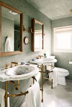 His and hers marble sinks in bathroom with penny tiled walls.