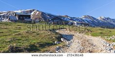 An early spring view on the Koschuta ridge in Karawanke mountains in Slovenia. Chalet named Kofce on the left and Alpine dairy farm on right are positioned in the middle of an alpine meadows.