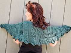 This shapely shawl features a Celtic inspired motif at the center, eyelet patterns on the wings and a cable and bobble edging. The center panel is worked first, side panels are worked sideways next and are tapered to the ends. The bottom band is worked last and features short row shaping at each bobble cluster to create a soft, scalloped edge.