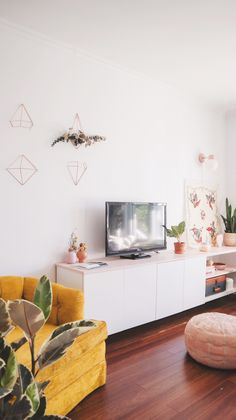 Modern meets Scandinavian living room decor with touches of pink and a vintage yellow armchair.