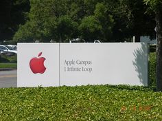 The Apple logo in red colour at an entrance to Apple's Cupertino campus....