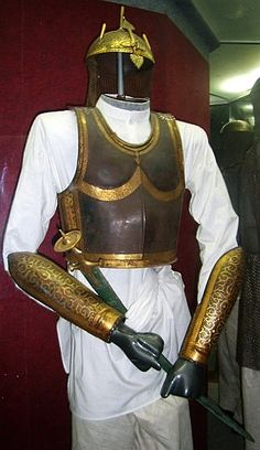 Indian (mughal) kulah khud (helmet) shown with an Indian steel cuirass in the European style, dastana / bazuband  (arm guards) and tulwar sword.  National Museum, New Delhi, India.