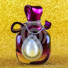 Purple, ornate perfume bottle wrapped in silver and pearl necklace on sparkling, yellow background.