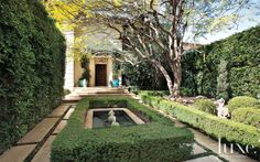 Sculpted hedges and a water feature in the entry courtyard set a formal tone, while stone frog statues from Inner Gardens lend a whimsical touch.