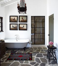 This Spanish style country home in California is designed by Kelley McDowell. She designed the shower door in the style of a metal casement window and chose Ojai river rock for the floor.   - HouseBeautiful.com