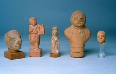 Agora Image: Roman terracotta figurines. Left to right: grotesque bearded head (T 3055), a child rattle as Apollo Kitharoidos (T 3444), Matrona (T 1989), two busts of infants (T 2937, T 713).