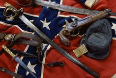 Confederate Artifacts: Civil War Confederate artifacts include a battle flag and a Confederate belt plate. The top saber appears homemade, while the other is government issue. The kepi is also government issue, but the knife is not. (