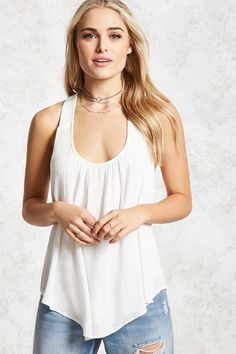 A crepe woven tank featuring a draped overlay construction, scoop neckline, sleeveless cut, an interior lining, and a tulip-back hem.