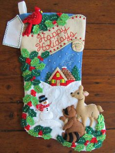 El pequeño muñeco de nieve parece estar apuntando el camino por el camino a la casa de campo acogedora caliente en el fondo en esta escena de vacaciones de invierno. Un pájaro cardenal rojo está encaramado en la parte superior de la media como un ciervo y mapache en la puntera de