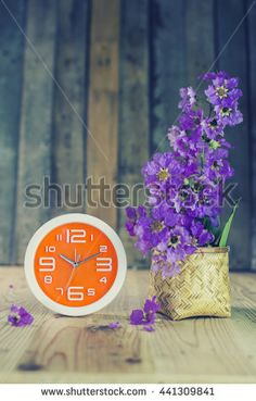 Orange wall clock and Flowers on a wooden table. Vintage Style. - stock photo