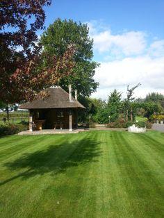 Landelijke tuin met grote gazons en een hooimijt