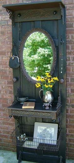 Recyclez une vieille porte, ajouter des crochets, un miroir, des équerres décoratives, des tablettes (une au centre et une en haut) des poignées (de chaque côté sous le miroir, un panier de métal et tout peindre en noir pour un vestibule à l'ancienne !