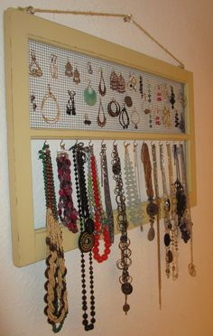 """My new jewelry holder made from:   old window frame  1/4"""" wire mesh (stapled on the back)  cup hooks  eye hooks   thick twine  glass drawer pull as the hanger"""
