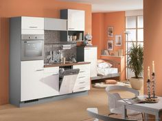 #Kitchen Idea of the Day: Small modern white kitchen by ALNO, AG, with peach/orange walls.