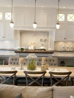 source: Alice Lane Home Open plan kitchen dining room with Visual Comfort Lighting Garey Pendants. Gray tufted dining settee with gray, weathered wood dining table and X-back bentwood chairs. White cabinetry with soapstone counters, white subway tiled ba