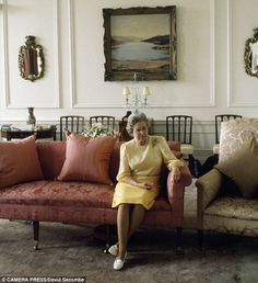 And relax: The Queen, elegant in a yellow checked dress and pearls, watches TV at Holyrood...