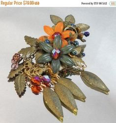This #vintage Colleen Toland flower brooch is just incredible and unique!  It features a cluster of enamel flowers with red AB rhinestone centers that are attached with clea... #ecochic #etsy #jewelry #jewellery