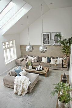 salon avec plafond sous pente et des fenetres, moquette gris meubles beiges