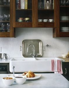 love this kitchen. rustic wood upper cabinets, white subway tile backsplash, white countertops, and black or more modern bottom cabinets. and of course... love the apron front sink.