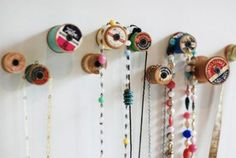Hang jewelry from old wooden spools mounted on the wall or a board.  Attach with a screw, looks like.
