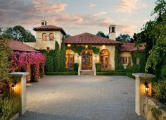 Mediterranean Exterior of Home with Arched window, Transom window, picture window, French doors, Raised beds, Deck Railing