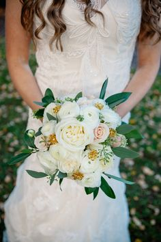 The bride carried an elegant winter bouquet of ivory garden roses, blush roses, white ranunculus, seeded eucalyptus, and gold jewels. | Photo by Jenny Storment Photography