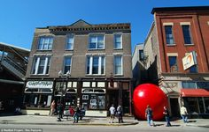 Rolling around the globe: Giant RedBall turning heads from Sydney to St Louis  Blocking the way: In Chicago, RedBall appears as if a it's a giant gumball rolling down the street