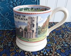 Emma Bridgewater, England 1/2 pint tea mug or coffee mug. The design of the mug is of a castle or church in the country with the saying or motto Find Peace In Ancient Places. The mug is part of the Na