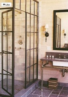 Shower with iron frame divider. Sinks are on both sides of room across from each other