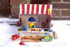 Basteln mit Kindern - Ideen für Weihnachten: In fast jeder Stadt finden in der Adventszeit Weihnachtsmärkte statt. Besuchen Sie doch mal mit Ihrem Kind einen Markt, essen Lebkuchen und trinken Punsch. Wenn Sie durchgefroren wieder zuhause sind, können Sie mit unserer kostenlosen Bastelanleitung einen Marktstand nachbasteln.
