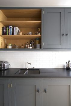 Sustainable Kitchens - Industrial Kitchen in Bath. Premium black honed granite worktops within oak shaker kitchen cabinetry painted in Farrow & Ball Down Pipe. Open oak shelving above a Stereo STD65 sink show off some extra storage. White metro tile splashback are visible. The high Georgian ceilings allow for taller and narrower units.