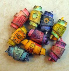8 bunte Gerollte perlen aus Polymer Clay. Sie wurden mit Kreiden coloriert und zweifach mit Satinlack versiegelt, jede fällt anders aus. Bestens geeignet für ein Armband oder mit Perlen aus Ihrem Fundus als Halskette. Sie bekomen 8 Perlen, die ich aussuche. Maße ca. 2,5 x 1,3 cm