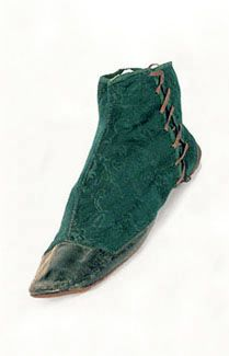 Damask gaiter boots, 1830s. Side-lacing half boots with toe and heel foxing of contrasting leather were called gaiter boots, because they resembled gaiters (spats) worn over shoes. This pair features deep green damask uppers lined with ecru cotton canvas twill and foxed with black leather. The boots lace up on one side with the original lacings. Though impractical for serious walking, gaiter boots make the foot appear dainty and genteel.
