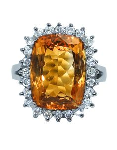 This cocktail ring is an absolute stunner! The 15x11 mm strikingly orange radiant cut citrine stone sits in a halo of prong set sparkling diamonds. There is a total diamond weight of .75 ct. The diamond prongs extend from the bridge of the ring, lifting the stones and creating an open gallery underneath. This ring is simply gorgeous!