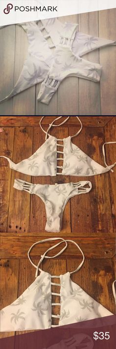Palm tree 🌴 fashion bikini White bikini with silver palm tree print. Top is like a halter and it ties around neck and in back. Top has built in cups. Bottoms are a cheeky style. Size run true to size. A medium would fit a 4-6 and large would fit 8-10. Open to offers. Swim Bikinis