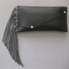 """Jessica Clutch $130.00         Super soft leather clutch.    Hand cut, hand sewn and made with love.    The purse is 13"""" x 6.5"""" and hangs 30"""" long, including the fringe. The fringe itself is 10"""" long (and can be totally customized to a shorter length if desired). And, how cool is this....the handle is detachable so you can swing it around or carry it under your arm."""